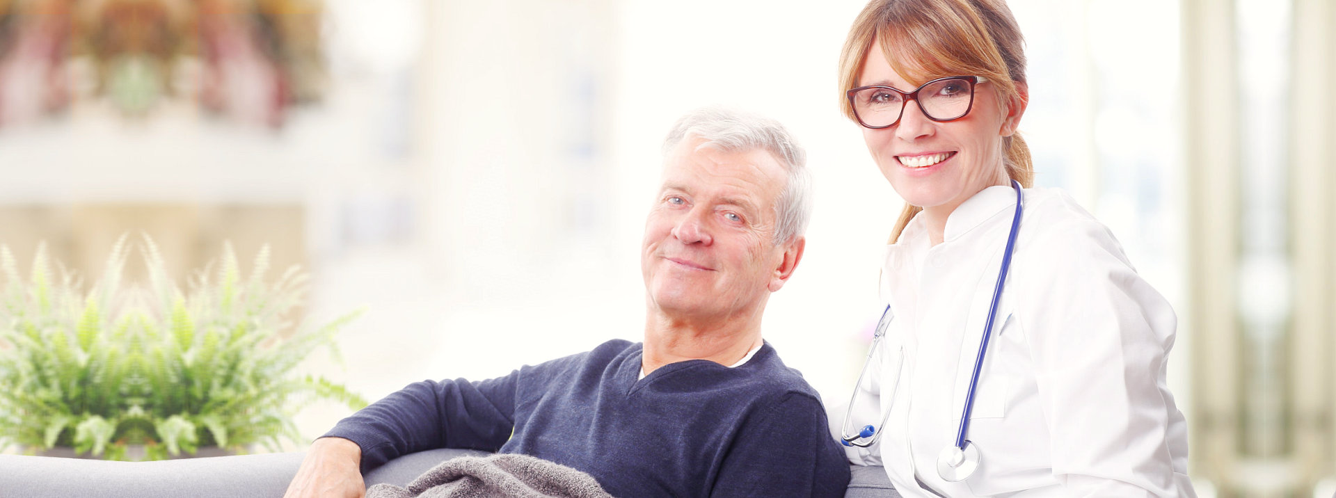 Man is sitting at the sofa with his nurse with eye glasses